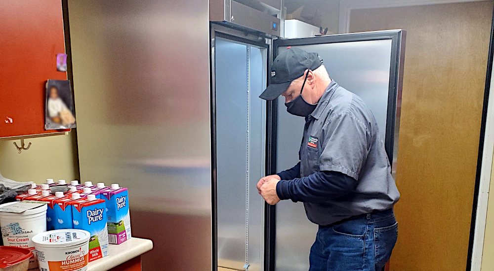 foodservice technician installing a commercial refrigerator